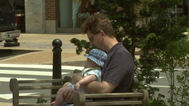 June 6 2008 CU Father dipping baby's feet into the fountain at strip mall park / Arlington Virginia United States