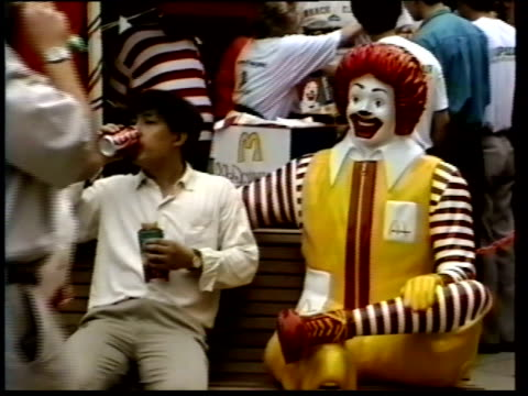 june 8, 1993 customer eating on park bench next to ronald mcdonald statue outside busy mcdonald's / china - fast food stock videos & royalty-free footage