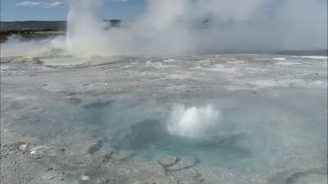 june tu several small geysers erupting in yellowstone national park, with steam rising above the gushing water / wyoming, united states - documentary footage stock videos and b-roll footage