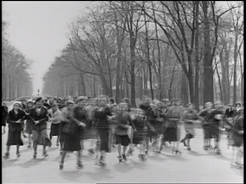 b/w 1934 junior catholic girls roller skating on street + holding hands / michigan / newsreel - 1934 stock videos & royalty-free footage