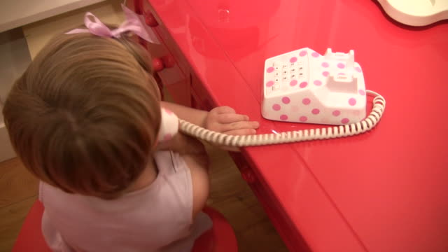 stockvideo's en b-roll-footage met (hd1080i) junior executive telephone skills; child talks on toy phone - lengte