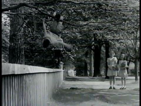 junior' hanging by legs upside-down in neighborhood tree friend walking wooden fence railing two girls standing on sidewalk watching smiling.... - time of day stock videos & royalty-free footage