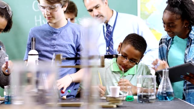 junior high age school students conduct science experiments in classroom. - stem topic stock videos & royalty-free footage