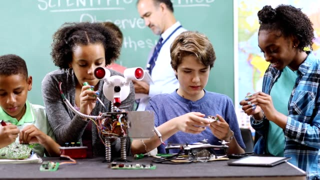 vídeos de stock e filmes b-roll de junior high school age students build robot in technology, engineering class. - stem assunto
