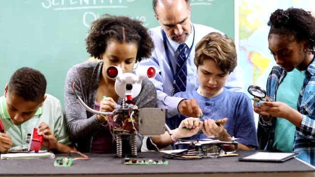 junior high school age students build robot in technology, engineering class. - secondary school child stock videos & royalty-free footage