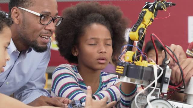 vídeos de stock e filmes b-roll de junior high school students building a robot in classroom - aluna da escola secundária