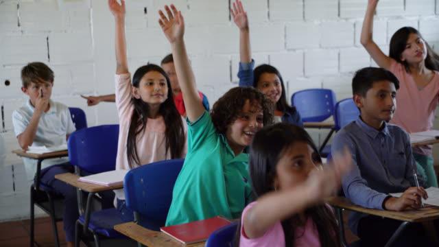 junior-high-studenten eifrig am unterricht teilnehmen, die hände heben - arme hoch stock-videos und b-roll-filmmaterial