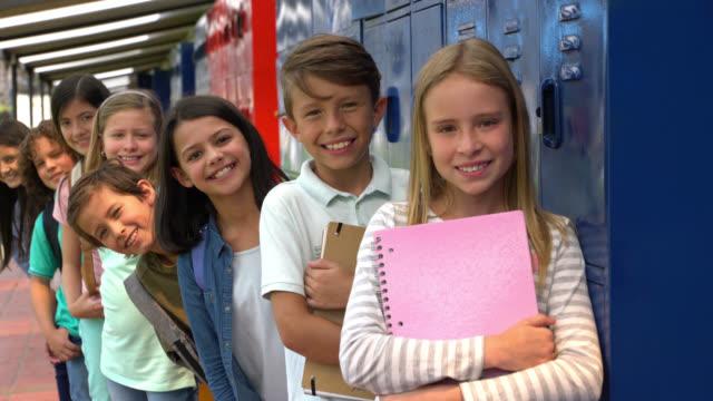 カメラでとても明るく微笑みながら、連続して立っている中学生 - ロッカー点の映像素材/bロール