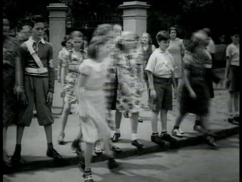 vídeos de stock e filmes b-roll de junior safety patrol boys blocking children at curb lowering arms allowing them to cross street ms another corner w/ patrol boys blocking children at... - baixar