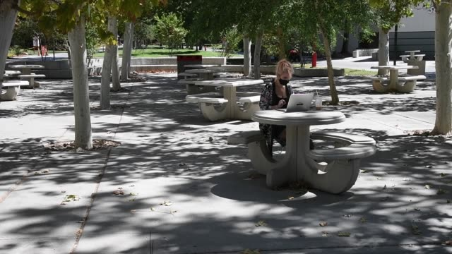 junior student kristina eichblatt works on a laptop in a courtyard on campus before attending a class at unlv amid the spread of the coronavirus on... - conference call stock videos & royalty-free footage