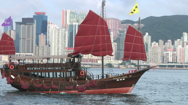 ms pan junk boat on river with downtown skyline behind / hong kong, china - dschunke stock-videos und b-roll-filmmaterial
