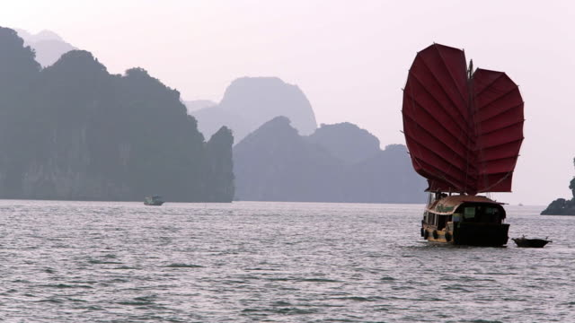vidéos et rushes de ws pan junk boat with red sails and passenger ship in bay / ha long bay, vietnam - jonque