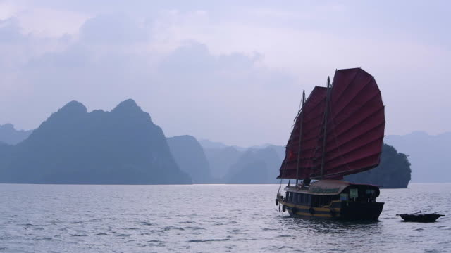 vidéos et rushes de ws junk boat with red sails in bay / ha long bay, vietnam - jonque