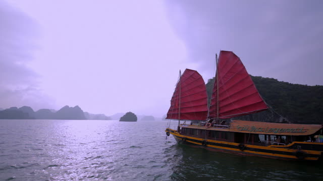 ws junk boat with red sails in bay / ha long bay, vietnam - halong bay stock videos and b-roll footage