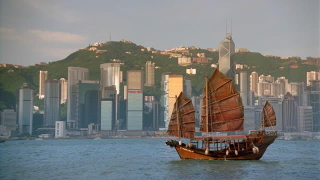 vídeos de stock e filmes b-roll de junk in harbor with hong kong skyline in background / central district - 1995