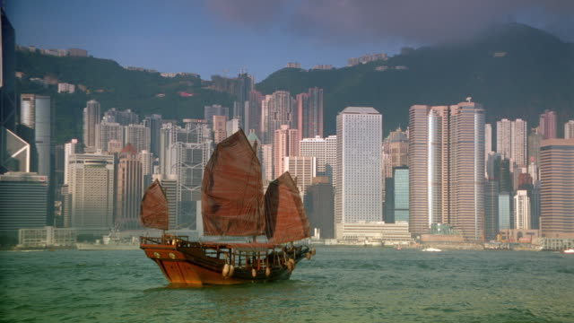 junk sailing in harbor with hong kong skyline in background / central district - central district hong kong stock videos & royalty-free footage