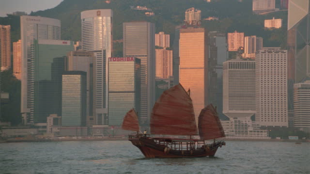 junk sailing past buildings in late afternoon / hong kong / wanchai - wanchai stock videos and b-roll footage