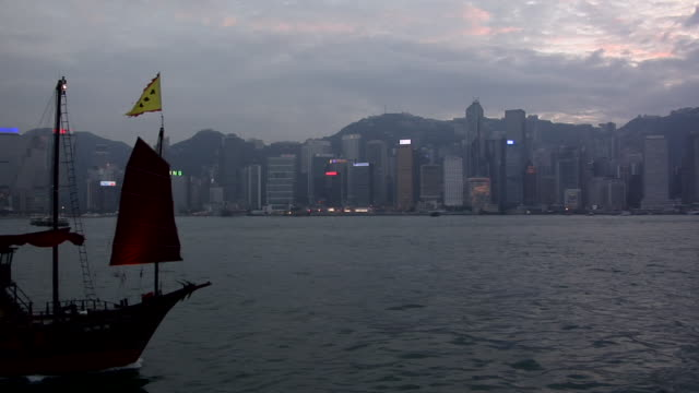 vidéos et rushes de ms, junk ship on pearl river, kowloon skyscrapers in background, hong kong, china - sampan