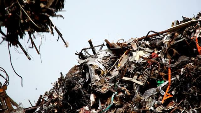 vidéos et rushes de a junkyard claw adds trash to a pile. - claw