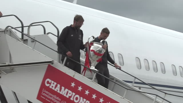 jurgen klopp and jordan henderson carrying the champions league trophy off the plane after landing at liverpool john lennon airport - final round stock videos & royalty-free footage