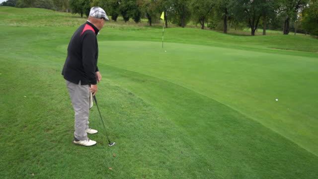 vídeos de stock, filmes e b-roll de just missing the hole on a long putt. - bolsa de golfe