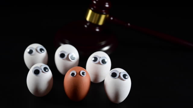 justice room. in the background a judge's gavel. in the foreground a dark egg with eyes and on both sides only white egg faces. racism concept. camera pan movement. - racism stock videos & royalty-free footage