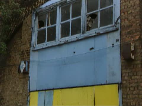 ; b)18.15 england: london: shoreditch: side press to garage under railway arch gv garage broken windows tilt down garage door - tilt down stock videos & royalty-free footage
