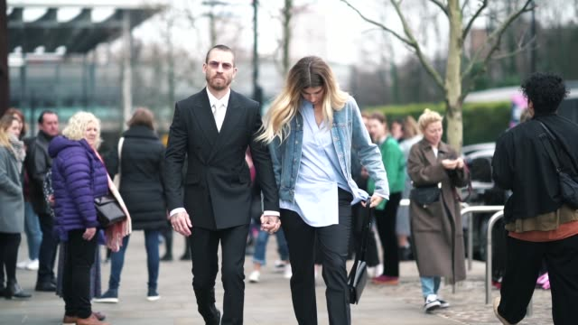 Justin O'Shea wears a black blazer jacket a shirt a tie Veronika Heilbrunner wears a necklace a blue denim jacket a shirt during London Fashion Week...