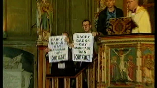 justin welby enthroned as archbishop of canterbury lib / tx protesters holding up posters reading 'carey backs gay marriage ban outrage' pull out... - カンタベリー大主教点の映像素材/bロール