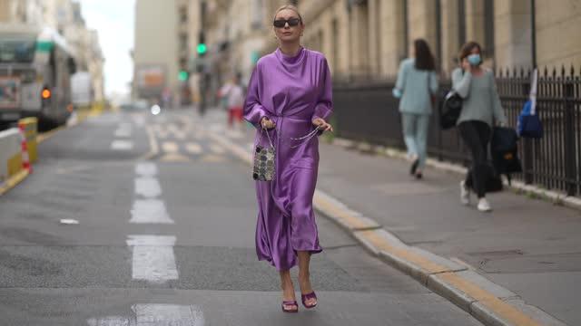 stockvideo's en b-roll-footage met justyna czerniak wears black sunglasses, gold earrings, a shiny purple turtleneck long sleeves flowing long dress, silver yoke handbag, purple shiny... - modeweek