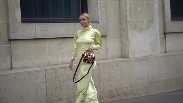 stockvideo's en b-roll-footage met justyna czerniak wears earrings a light yellow hineck puff sleeves asymmetric long dress a chloe orange brown and white bag mesh heels outside ann... - jurk