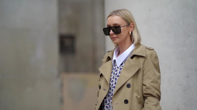 justyna czerniak wears sunglasses, a beige trench coat, a blue and white floral print pleated dress with white collar, a blue quilted bottega veneta... - トレンチコート点の映像素材/bロール