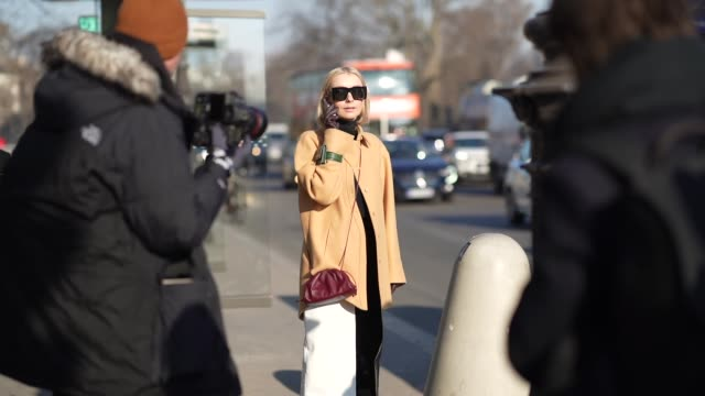 stockvideo's en b-roll-footage met justyna czerniak wears sunglasses a black turtleneck pullover a light brown coat a black and white shiny skirt purple leather boots gloves outside... - coltrui