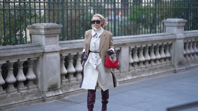 stockvideo's en b-roll-footage met justyna czerniak wears sunglasses a light brown oversized jacket a white turtleneck a gray dress with buttons a red bag purple leather high heeled... - coltrui