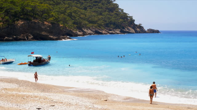 kabak beach surf with swimmers and small boats. - marmaris stock videos & royalty-free footage