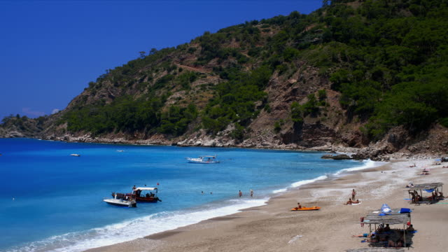 kabak beach total with boats, swimmers and beach goers. pan left. - marmaris stock videos & royalty-free footage