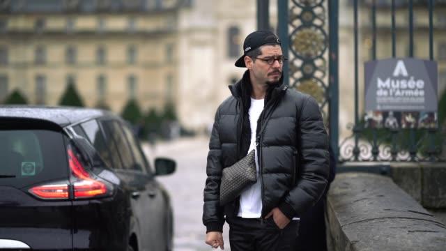 Kadu Dantas wears a cap a Goyard bag a black puffer coat white sneakers with colored shoe lace outside Maison Margiela during Paris Fashion Week...