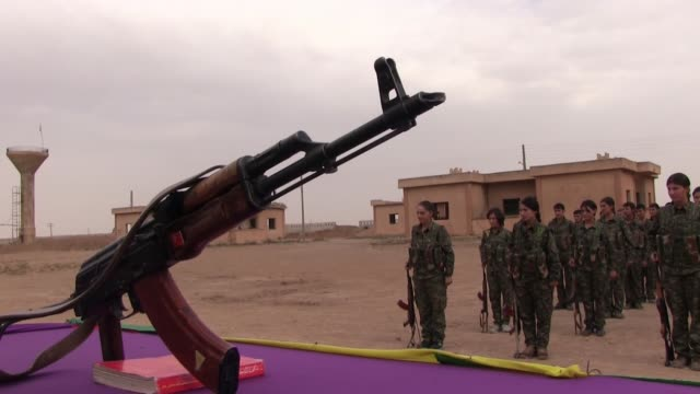 kalashnikov ak-47 rifle placed on a table during swearing ceremony of kurdish fighters of the women's protection units ypj in a training camp on... - people's protection units stock videos & royalty-free footage