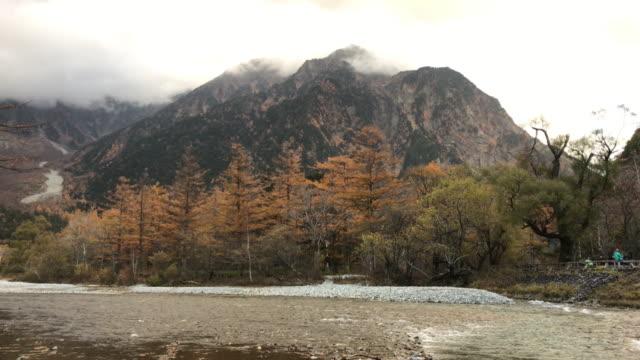 vídeos de stock, filmes e b-roll de kamikoshi gama de mountain view com rio e árvore na província de nagano nevoeiro, japão - estampa de folha