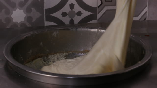 kanafeh. view of kanafeh soft nabulsi cheese, an ingredient of kanafeh, being turned in a bowl. - sticky stock videos & royalty-free footage