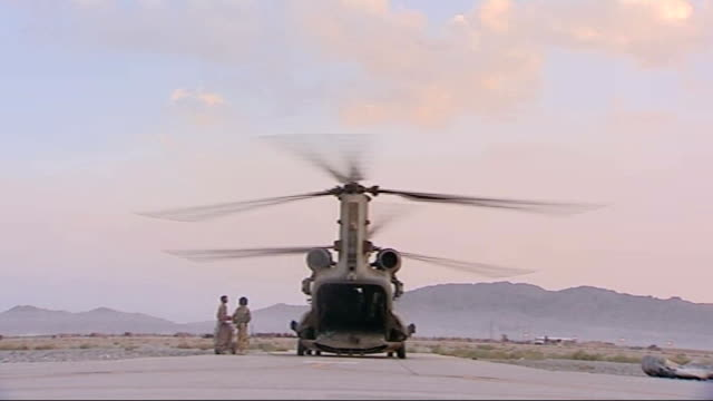 kandahar airbase ext british military chinook helicopter with rotors turning on runway at kandahar airfield british paratroopers on runway waiting to... - helicopter rotors stock videos and b-roll footage