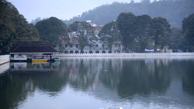 vídeos de stock e filmes b-roll de kandy lake and the temple of the sacred tooth relic (temple of the tooth, sri dalada maligawa) at dawn, kandy, central province, sri lanka, asia  - cultura cingalesa