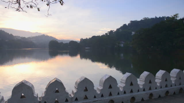 kandy lake and the temple of the sacred tooth relic (temple of the tooth, sri dalada maligawa) at sunrise, kandy, central province, sri lanka, asia  - sri lankan culture stock videos & royalty-free footage
