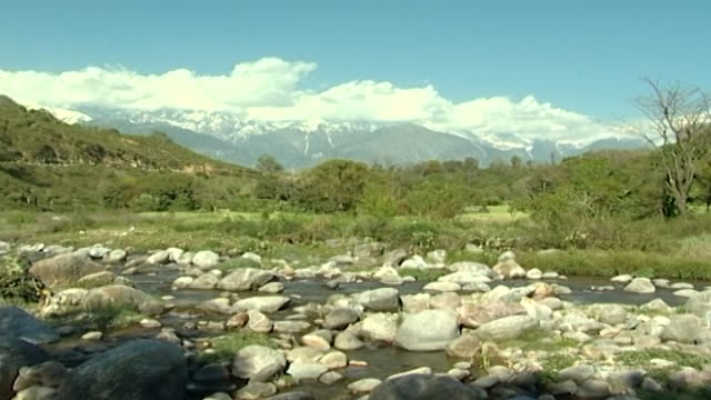 vídeos de stock e filmes b-roll de kangra valley, dharamsala. a boulder-filled glacial river with a lush, tree-covered landscape and snow-capped mountains in the background. - pinaceae