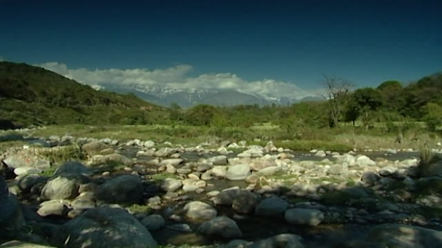 vídeos de stock, filmes e b-roll de kangra valley, dharamsala. a boulder-filled river with a rich and varied, tree-covered landscape and snow-capped mountains in the background. - boulder rock