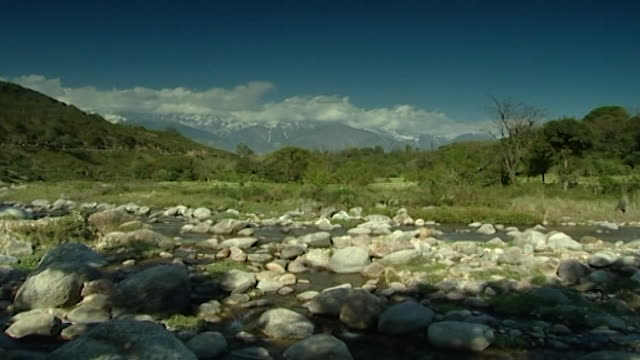 kangra valley, dharamsala. from a boulder-filled river to a tree-covered landscape with cloud-covered, snow-capped mountains in the background. - boulder rock stock videos & royalty-free footage