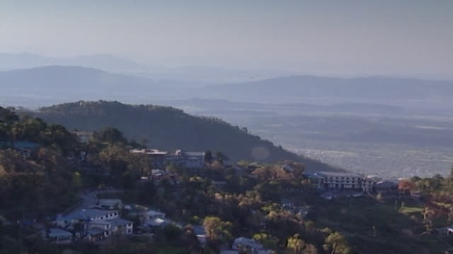 kangra valley, dharamsala.pan-right of the mountainous, tree-covered landscape with homes nestled into the mountain-side. - pinaceae stock videos & royalty-free footage