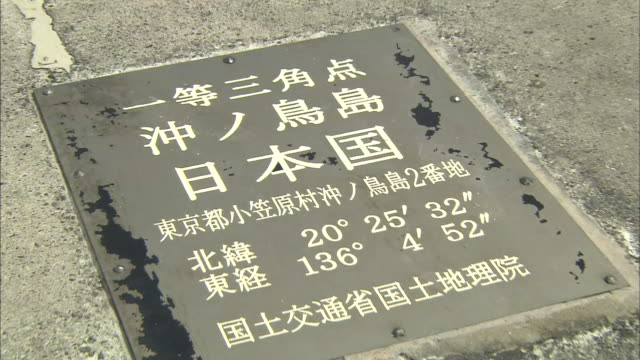 vídeos y material grabado en eventos de stock de kanji characters and numerals on a plaque provide the nautical coordinates for higashi-kojima in okinotorishima island, japan. - okinotorishima