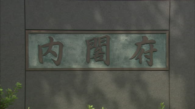 Kanji characters on a metal plaque identify the Cabinet Office Building in Tokyo.