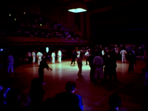 vidéos et rushes de karate match in progress / an asian man in black gi uniform with red belt competes against redheaded man in white gi uniform with black belt / man in... - karaté